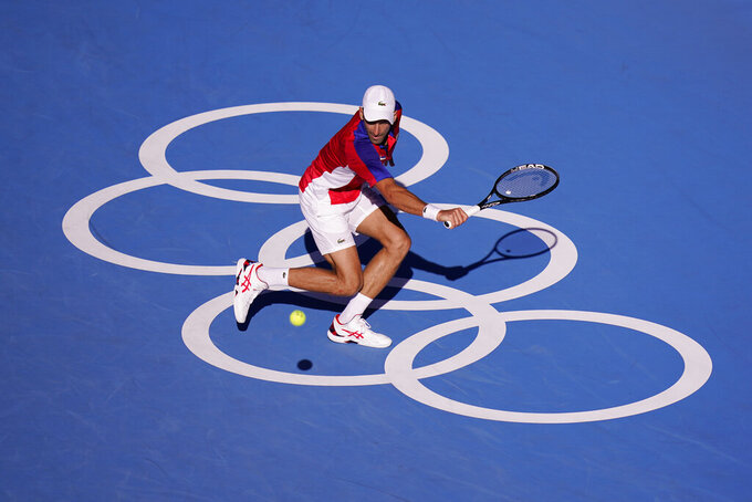 Novak Djokovic, of Serbia, returns a shot to Pablo Carreno Busta, of Spain, during the bronze medal match of the tennis competition at the 2020 Summer Olympics, Saturday, July 31, 2021, in Tokyo, Japan. (AP Photo/Seth Wenig)