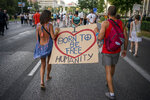 Demonstrators carry a placard during a protest in Madrid, Spain, Saturday, Aug. 14, 2021. Protesters are rallying to show their opposition to vaccinating children against COVID-19 . (AP Photo/Andrea Comas)