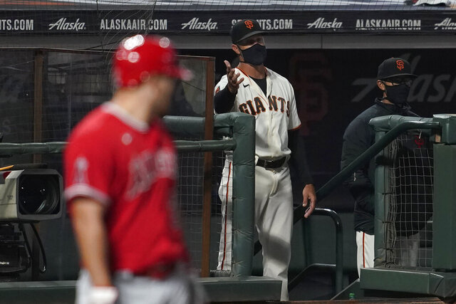 San Francisco Giants manager Gabe Kapler gestures toward umpires as Los Angeles Angels' Mike Trout, left, stands at the plate during the seventh inning of a baseball game in San Francisco, Thursday, Aug. 20, 2020. (AP Photo/Jeff Chiu)