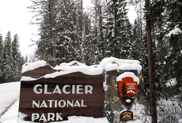FILE - In this Dec. 11, 2012, file photo, snow covers the entrance sign to Glacier National Park in West Glacier, Mont. Three more of America's most popular national parks have closed their gates as pressure mounts on superintendents to prevent crowded trails that could lead to more spread of the coronavirus even as the Trump administration sticks to its decision to waive entrance fees at the parks. Glacier in Montana and Arches and Canyonlands in Utah announced their decisions to close Friday, March 27, 2020, just days after several other well-known parks such as Yellowstone, Grand Teton and the Great Smoky Mountains did the same. (AP Photo/Matt Volz, File)