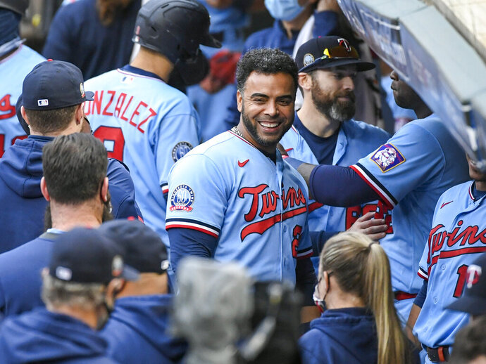 FILE  - In this Sept. 27, 2020, file photo, Minnesota Twins' Nelson Cruz, center, smiles in the dugout after the Twins clinched the AL Central championship with the Chicago White Sox's loss during the tenth inning of a baseball game in Minneapolis. Twins designated hitter Nelson Cruz was voted Marvin Miller Man of the Year and Atlanta Braves first baseman Freddie Freeman was picked as Player of the Year in annual Players Choice award voting by the Major League Baseball Players Association.(AP Photo/Craig Lassig, File)
