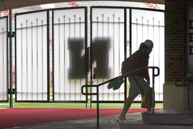 A player carries his shoes and a lunch bag in front of a closed gate leading to Memorial Stadium's playing field in Lincoln, Neb., Wednesday, Aug. 12, 2020. The Big Ten won't play football this fall because of concerns about COVID-19, becoming the first of college sports' power conferences to yield to the pandemic. The move announced Tuesday. (AP Photo/Nati Harnik)