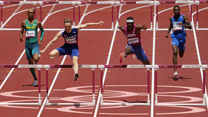 Karsten Warholm, of Norway, second left, clears the final hurdle before winning the gold medal ahead of Rai Benjamin, of United States in the final of the men's 400-meter hurdles at the 2020 Summer Olympics, Tuesday, Aug. 3, 2021, in Tokyo, Japan. (AP Photo/Charlie Riedel)