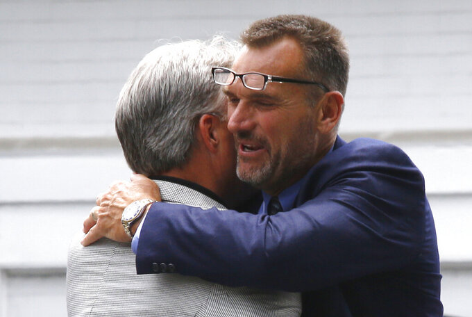 FILE- In this June 16, 2014, file photo, former Pittsburgh Steelers offensive lineman Tunch Ilkin, right, hugs Mike O'Donnell, the brother of former Steelers quarterback Neil O'Donnell, as they arrive for a viewing for former Pittsburgh Steelers head football coach Chuck Noll in Pittsburgh.  Ilkin, a Turkis-born two-time Pro Bowl offensive lineman with the Pittsburgh Steelers in the 1980s who went on to become a beloved member of the organization's broadcast team, died on Saturday morning, Sept. 4, 2021, the team said. He was 63. Ilkin, who revealed last fall he was fighting amyotrophic lateral sclerosis (also known as Lou Gehrig's Disease), had been hospitalized recently with pneumonia. (AP Photo/Keith Srakocic, File)
