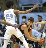 Northeastern's Coleman Stucke (15) is trapped by North Carolina's Kerwin Walton (24) during the first half of an NCAA college basketball game Wednesday, Feb. 17, 2021, in Chapel Hill, N.C. (Robert Willett/The News & Observer via AP)