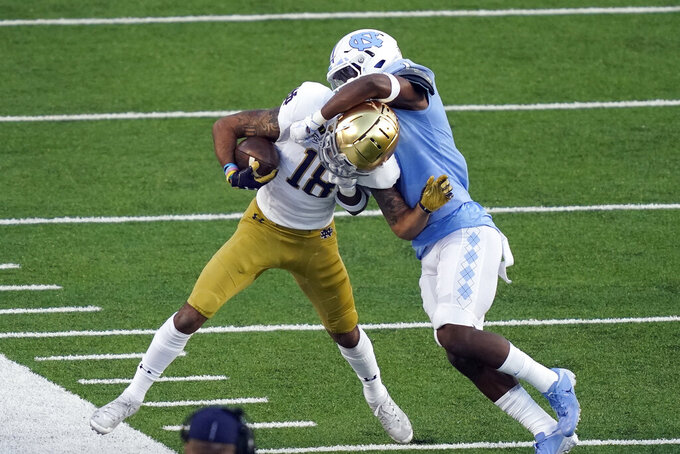 North Carolina defensive back Kyler McMichael (1) tackles Notre Dame wide receiver Joe Wilkins Jr. (18) during the first half of an NCAA college football game in Chapel Hill, N.C., Friday, Nov. 27, 2020. (AP Photo/Gerry Broome)