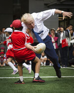 FILE - In this Oct. 15, 2015 file photo, Boris Johnson takes part in a Street Rugby tournament in a Tokyo street. (Stefan Rousseau/PA via AP)