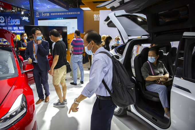 Visitors wearing face masks to protect against the coronavirus look at Tesla vehicles on display at the China International Fair for Trade in Services (CIFTIS) in Beijing, Saturday, Sept. 5, 2020. Auto executives are flying in early to wait out a coronavirus quarantine ahead of the Beijing auto show, the year's biggest sales event for a global industry that is struggling with tumbling sales and layoffs. Organizers say they will impose intensive anti-disease controls on crowds and monitor visitors and employees for signs of infection. (AP Photo/Mark Schiefelbein)