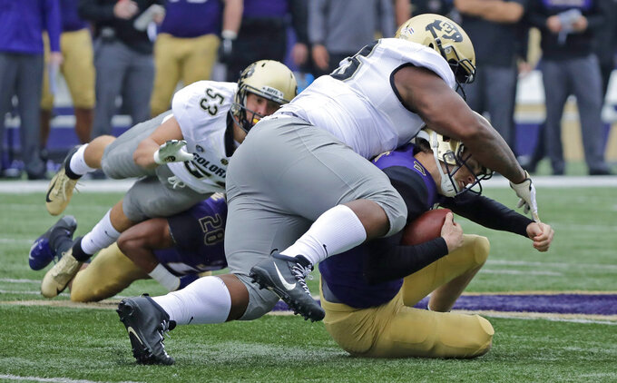 Washington quarterback Jake Browning, lower right, is tackled by Colorado's Javier Edwards, upper right, during the first half of an NCAA college football game, Saturday, Oct. 20, 2018, in Seattle. (AP Photo/Ted S. Warren)