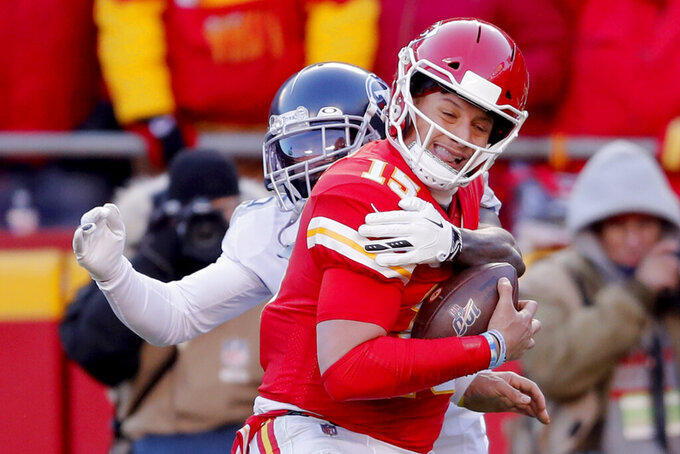 Kansas City Chiefs' Patrick Mahomes (15) runs for a touchdown against Tennessee Titans defensive tackle DaQuan Jones, rear, during the first half of the NFL AFC Championship football game Sunday, Jan. 19, 2020, in Kansas City, MO. (AP Photo/Jeff Roberson)