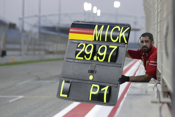 A Ferrari team member shows a pit board to Mick Schumacher during his first F1 test for Ferrari at the Bahrain International Circuit in Sakhir, Bahrain, Tuesday, April 2, 2019. Mick Schumacher has moved closer to emulating his father Michael by driving a Ferrari Formula One car in an official test. Schumacher's father won seven F1 titles, five of those with Ferrari and holds the record for race wins with 91. (AP Photo/Hassan Ammar)