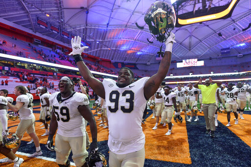 Wake Forest offensive lineman Loic Ngassam Nya (59) and defensive lineman Isaiah Chaney (93) celebrate after a 40-37 overtime win against Syracuse in an NCAA college football game in Syracuse, N.Y., Saturday, Oct. 9, 2021. (AP Photo/Adrian Kraus)