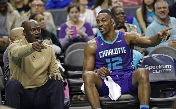 Charlotte Hornets owner Michael Jordan, left, talks with Dwight Howard, right, during the first half of the team's NBA basketball game against the Utah Jazz in Charlotte, N.C., Friday, Jan. 12, 2018. (AP Photo/Chuck Burton)