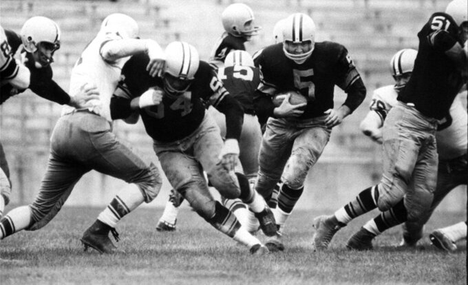 """FILE - In this Aug. 10, 1959 file photo, Paul Hornung (5) of the Green Bay Packers goes through the line in an inter-squad game in Green Bay, Wis. Hornung, the dazzling """"Golden Boy"""" of the Green Bay Packers whose singular ability to generate points as a runner, receiver, quarterback, and kicker helped turn them into an NFL dynasty, has died, Friday, Nov. 13, 2020. He was 84. (AP Photo, File)"""