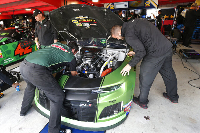 The crew for Chase Elliott work on his car in the garage at Martinsville Speedway In Martinsville, Va., Saturday, Oct. 26, 2019. Elliott had an engine failure less than five minutes into the opening practice for the third round of NASCAR's playoffs. (AP Photo/Steve Helber)