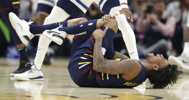 Cleveland Cavaliers' Kevin Porter Jr. holds his knee after an injury in the second half of an NBA basketball game against the Minnesota Timberwolves, Sunday, Jan. 5, 2020, in Cleveland. Porter left the game due to the injury. Minnesota won 118-103. (AP Photo/Tony Dejak)