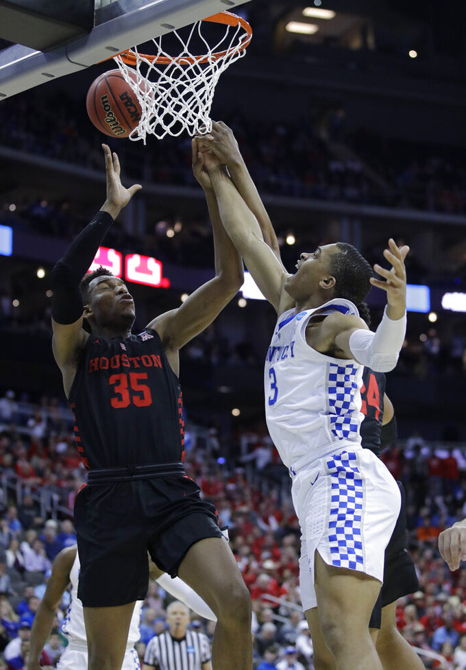 Kentucky's Keldon Johnson, right, knocks the ball away from Houston's Fabian White Jr. (35) during the first half of a men's NCAA tournament college basketball Midwest Regional semifinal game Friday, March 29, 2019, in Kansas City, Mo. (AP Photo/Charlie Riedel)