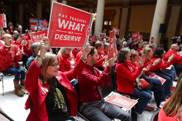FILE - In this April 16, 2019 file photo, teachers cheer during a rally at at the Statehouse in Indianapolis. Indiana Gov. Eric Holcomb isn't promising any quick action on the call for further boosting teacher pay that thousands of educators will be making at the Statehouse next week. Teacher unions say at least 107 school districts with more than 40 percent of Indiana's students will be closed Tuesday, Nov. 19, 2019, while their teachers attend the rally. Holcomb didn't criticize school districts for closing, saying it was a local decision. (AP Photo/Michael Conroy, File)