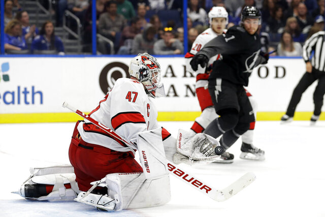 Carolina Hurricanes goaltender James Reimer (47) makes a glove save against the Tampa Bay Lightning during the second period of an NHL hockey game, Saturday, Nov. 30, 2019, in Tampa, Fla. (AP Photo/Chris O'Meara)