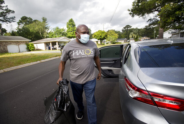 In this Friday, May 14, 2020 photo, Robert Ellington with HALOS nonprofit drops off diapers to a family in need in North Charleston, S.C. Advocates worry that elevated family stress, increased financial burdens and extended school closures mean that many children across South Carolina remain.  (Andrew J. Whitaker/The Post And Courier via AP)