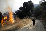 FILE - In this Oct. 12, 2019, file photo, a firefighter runs up a fire road to hose down flames from a wildfire in Newhall, Calif. Fire danger remains high as dry, warm winds blow through Southern California. The National Weather Service says gusts on Sunday, Oct. 20, could top 60 mph (97 kph) in some parts of Los Angeles, Ventura and Santa Barbara counties. Southern California Edison says it's monitoring conditions to determine whether preventive power shut-offs will be needed. (AP Photo/Marcio Jose Sanchez)
