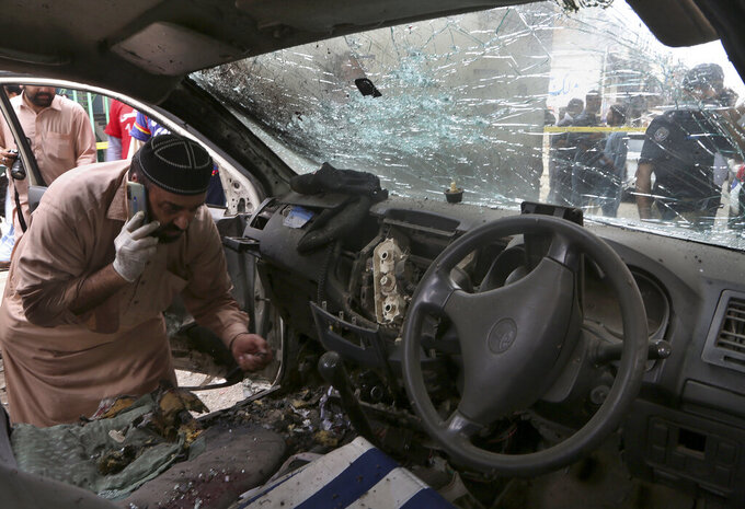 An investigator examines a damaged police vehicle at the site of hand grenade attack in Peshawar, Pakistan, Friday, July 30, 2021. Attackers threw a hand grenade at a police van in Pakistan's northwestern city of Peshawar on Friday, killing and wounding police officers before fleeing the scene, police said. (AP Photo/Muhammad Sajjad)