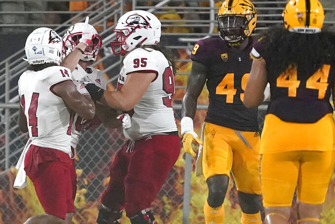 Southern Utah wide receiver Judd Cockett celebrates his touchdown against Arizona State with defensive lineman Mark Kruger (95) and wide receiver Lance Lawson (14) during the first half of an NCAA college football game, Thursday, Sept. 2, 2021, in Tempe, Ariz. (AP Photo/Matt York)