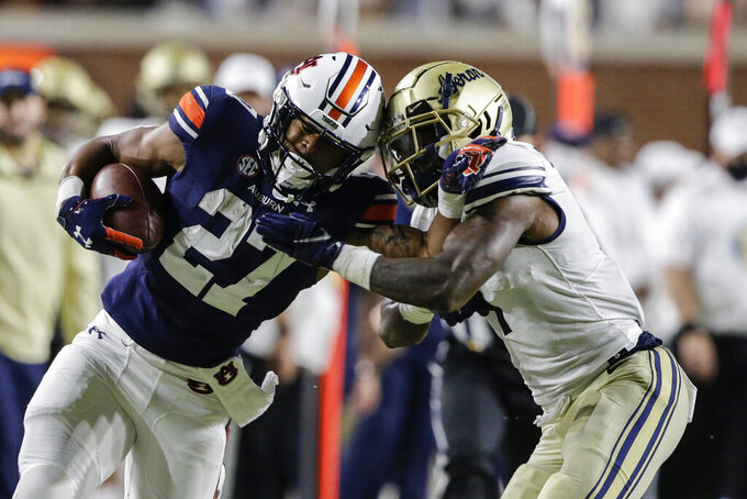 Auburn running back Jarquez Hunter (27) is pushed out of bounds by Akron cornerback Randy Cochran Jr. (1) during the second half of an NCAA college football game Saturday, Sept. 4, 2021, in Auburn, Ala. (AP Photo/Butch Dill)