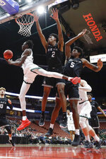 Hawaii guard Sheriff Drammeh drives to the basket past Long Beach State's Mason Riggins, right, and Jordan Roberts during first half of an NCAA college basketball game at the Big West men's tournament in Anaheim, Calif., Thursday, March 14, 2019. (AP Photo/Chris Carlson)