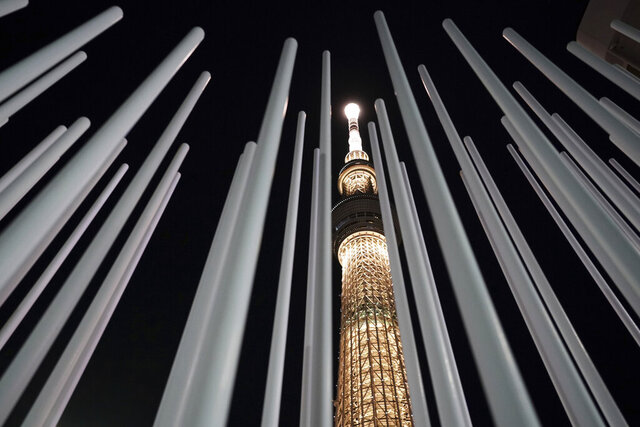 The Tokyo Skytree, the tallest tower in Japan, is illuminated with the color of the Olympic Torch, to commemorate 100 days until the torch relay begins, Tuesday, Dec. 15, 2020, in Tokyo. (AP Photo/Eugene Hoshiko)