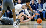 Villanova guard Justin Moore (5) and Xavier forward Zach Freemantle (32) dive for a loose ball during the first half of an NCAA college basketball game, Monday, Dec. 30, 2019, in Villanova, Pa. (AP Photo/Laurence Kesterson)