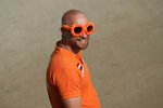 An orange-clad fan is on his way to watch the first free practice session ahead of Sunday's Formula One Dutch Grand Prix at the Zandvoort racetrack, Netherlands, Friday, Sept. 3, 2021. (AP Photo/Francisco Seco)