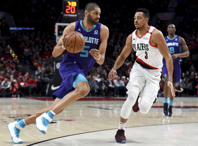 Charlotte Hornets forward Nicolas Batum, left, drives to the basket on Portland Trail Blazers guard CJ McCollum, right, during the first half of an NBA basketball game in Portland, Ore., Friday, Jan. 11, 2019. (AP Photo/Steve Dykes)