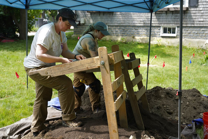 University of Massachusetts Boston research scientist Christa Beranek, of Arlington, Mass., left, and UMass graduate student Emily Willis, of Boston, right, sift soil through screens while searching for artifacts at an excavation site, Wednesday, June 9, 2021, on Cole's Hill, in Plymouth, Mass. The archaeologists are part of a team excavating the grassy hilltop that overlooks iconic Plymouth Rock one last time before a historical park is built on the site. (AP Photo/Steven Senne)