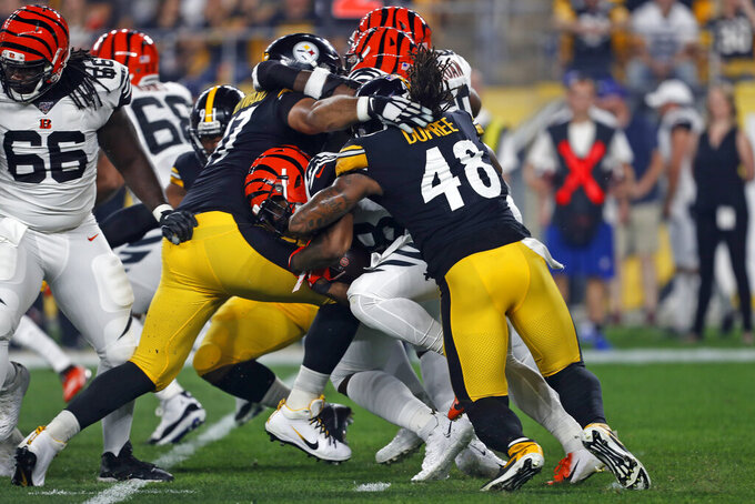 Cincinnati Bengals running back Joe Mixon, center, is tackled by Pittsburgh Steelers defensive end Cameron Heyward, left, and outside linebacker Bud Dupree (48) during the first half of an NFL football game in Pittsburgh, Monday, Sept. 30, 2019. (AP Photo/Tom Puskar)