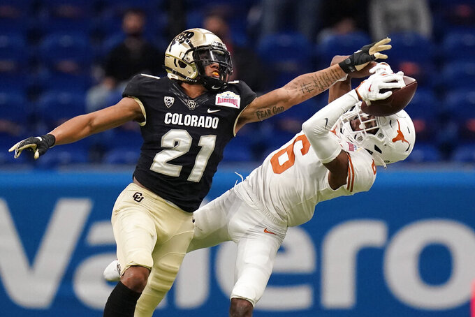 Colorado cornerback Christian Gonzalez (21) breaks up a pass intended for Texas wide receiver Joshua Moore (6) during the first half of the Alamo Bowl NCAA college football game Tuesday, Dec. 29, 2020, in San Antonio. (AP Photo/Eric Gay)