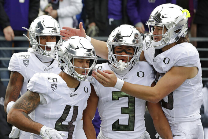 Oregon quarterback Justin Herbert, right, reaches over Johnny Johnson III (3) to congratulate Mycah Pittman (4) on Pittman's 36-yard touchdown reception against Washington in the second half of an NCAA college football game Saturday, Oct. 19, 2019, in Seattle. Oregon won 35-31. (AP Photo/Elaine Thompson)