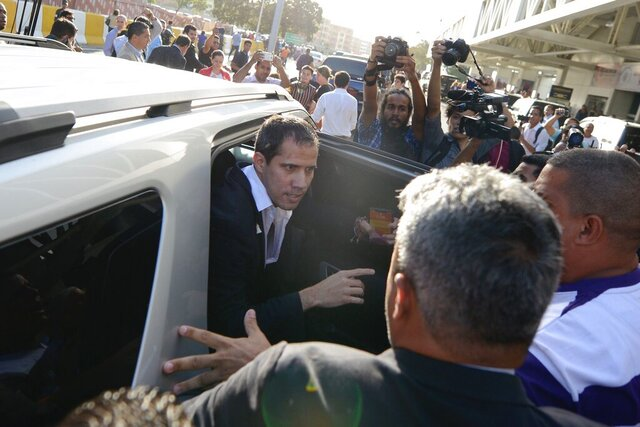 Surrounded by supporters of Venezuela's President Nicolas Maduro and members of the media, opposition leader Juan Guaido boards a vehicle after arriving at the Simon Bolivar International Airport in La Guaira, Venezuela, Tuesday, Feb. 11, 2020. Guaido returned home from a tour of nations that back his effort to oust socialist leader Nicolas Maduro. (AP Photo/Matias Delacroix)