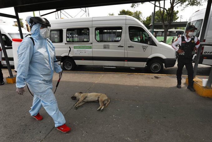 A member of cleaning crew wearing protective mask and suit walk after disinfecting a bus as a preventive measure against the spread of the new coronavirus, in Mexico City, Thursday, April 2, 2020. Mexico has started taking tougher measures against the new coronavirus, but some experts warn the country is acting too late and testing too little to prevent the type of crisis unfolding across the border in the United States. (AP Photo/Marco Ugarte)