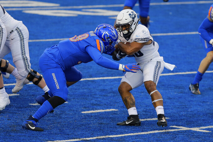 Utah State running back Jaylen Warren (20) spins way from Boise State defensive tackle Scott Matlock (99) in the first half in an NCAA college football game Saturday, Oct. 24, 2020, in Boise, Idaho. (AP Photo/Steve Conner)