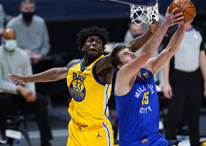 Denver Nuggets center Nikola Jokic, front, drives to the rim for a reverse dunk basket past Golden State Warriors center James Wiseman in the first half of an NBA basketball game Thursday, Jan. 14, 2021, in Denver. (AP Photo/David Zalubowski)