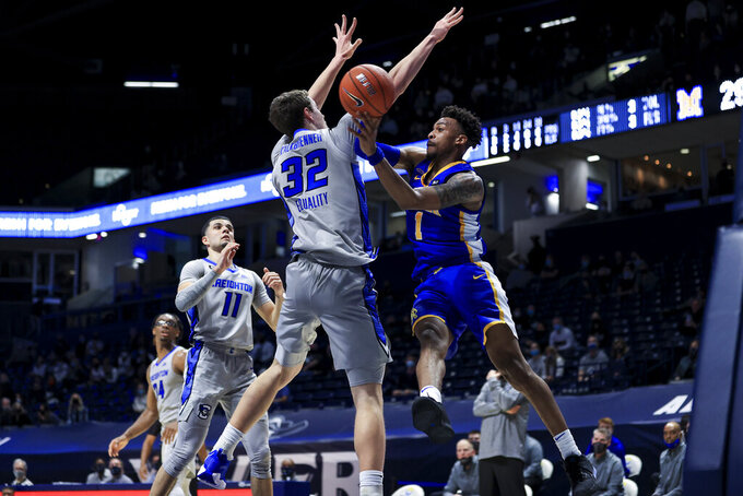 Creighton center Ryan Kalkbrenner, left, defends as Xavier guard Paul Scruggs passes the ball in the first half of an NCAA college basketball game, Saturday, Feb. 27, 2021, in Cincinnati. (AP Photo/Aaron Doster)