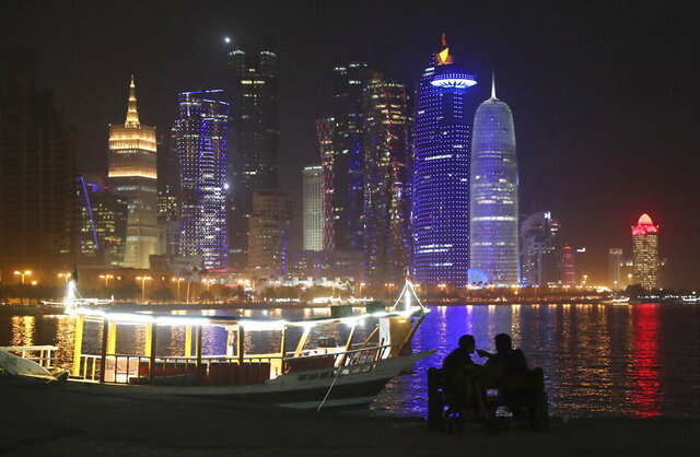 FILE - In this May 14, 2019 file photo, two people take in the sea breeze at the Corniche waterfront promenade in Doha, Qatar. The small, neighboring sheikhdoms of Bahrain and Qatar have the world's highest per capita rates of coronavirus infections in the world. In the two Mideast countries, COVID-19 epidemics initially swept undetected through camps housing healthy and young foreign laborers. In Qatar, a new study found that nearly 60% of those testing positive showed no symptoms at all. In Bahrain, authorities put the number of asymptomatic spreaders of the virus even higher, at 68%. (AP Photo/Kamran Jebreili, File)