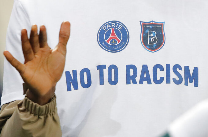 A 'No To Racism' logo on the shirt of Basaksehir assistant coach Pierre Webo prior to the Champions League group H soccer match between Paris Saint Germain and Istanbul Basaksehir at the Parc des Princes stadium in Paris, France, Wednesday, Dec. 9, 2020. The match is resuming on Wednesday with a new refereeing team after players from Paris Saint-Germain and Istanbul Basaksehir left the field on Tuesday evening and didn't return when the fourth official — Sebastian Coltescu of Romania — was accused of using a racial term to identify Basaksehir assistant coach Pierre Webo before sending him off for his conduct on the sidelines. (AP Photo/Francois Mori)
