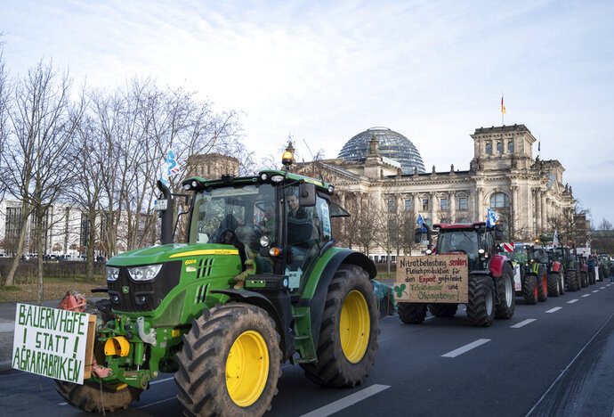 Farmers drive past the Reichstag building with their tractors in Berlin, Saturday, Jan.18, 2020. On the occasion of the Green Week agricultural and food fair, people in Berlin demonstrate for more environmentally friendly agriculture. (Christophe Gateau/dpa via AP)