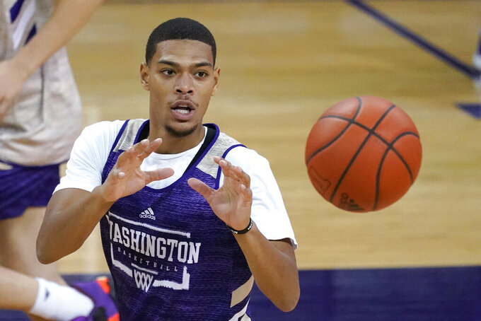 Washington's Quade Green reaches for the ball during an NCAA college basketball practice Tuesday, Oct. 27, 2020, in Seattle. Green is back after missing half of last season due to academic ineligibility that sent the Huskies season into a spiral. (AP Photo/Elaine Thompson)