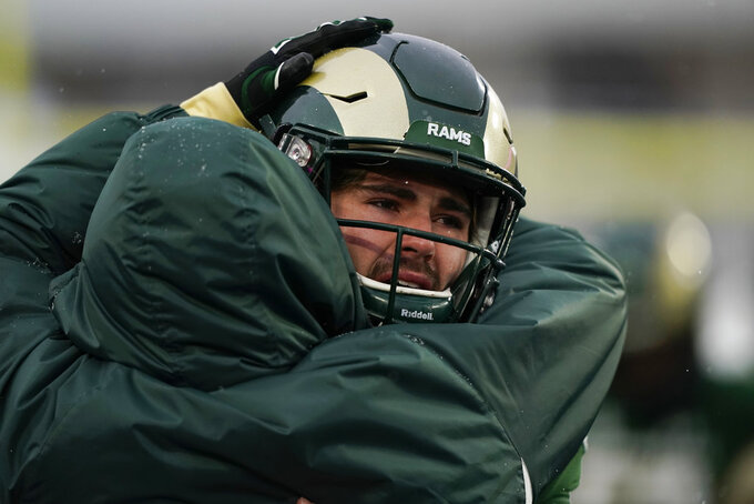 Colorado State quarterback Collin Hill is consoled after the team's 29-24 loss to Utah State during an NCAA football game Saturday, Nov. 17, 2018, in Fort Collins, Colo. (AP Photo/Jack Dempsey)