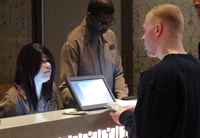 In this March 21, 2019 photo, a gambler places a bet on the NCAA men's college basketball tournament at the Borgata casino in Atlantic City N.J. Figures released on Friday, April 12, 2019, show gamblers bet $372.4 million on sports in New Jersey in March, the second-highest monthly total ever, with the March Madness tournament accounting for a significant part of the wagering. (AP Photo/Wayne Parry)