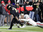 FILE - In this Saturday, Oct. 20, 2018, file photo, Purdue's Rondale Moore (4) scores a touchdown after breaking the tackle of Ohio State safety Isaiah Pryor (12) during the first half of an NCAA college football game in West Lafayette, Ind. Freshman sensation Rondale Moore looks to keep piling up yards in Purdue's visit to Michigan State this Saturday. (AP Photo/Michael Conroy, File)