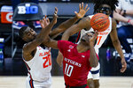 Illinois guard Da'Monte Williams (20) blocks the shot of Rutgers guard Montez Mathis (10) during the first half of an NCAA college basketball game at the Big Ten Conference men's tournament in Indianapolis, Friday, March 12, 2021. (AP Photo/Michael Conroy)